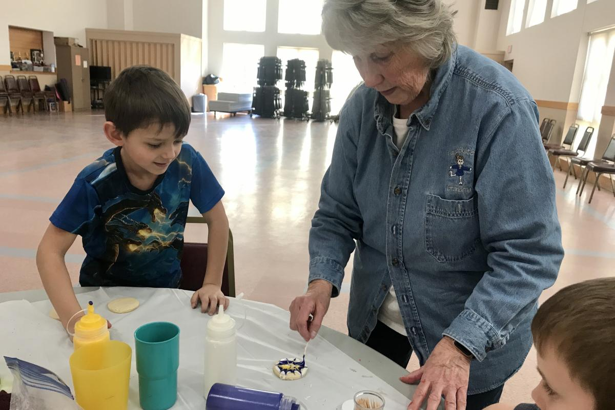 Grandparents decorating cookies with grandchildren by Carla Grabiec